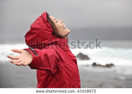 Rain. Woman enjoying a grey rainy fall day on the beach. Young smiling woman in red raincoat. - stock photo