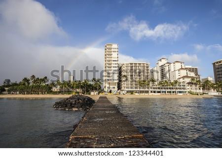 Rainbow above Waikiki high rise towers. - stock photo