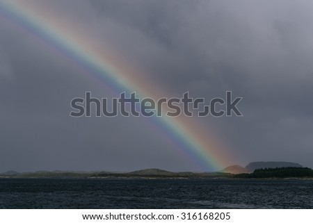 Rainbow after a storm over the sea - stock photo
