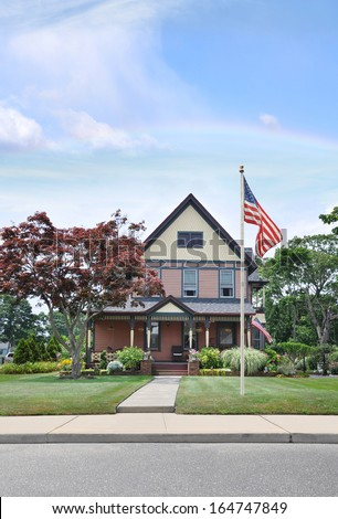Rainbow American Flag Pole Suburban Victorian Style Home Landscaped Front yard lawn Flowers Plants Cement Sidewalk Residential Neighborhood Blue Sky Clouds USA - stock photo