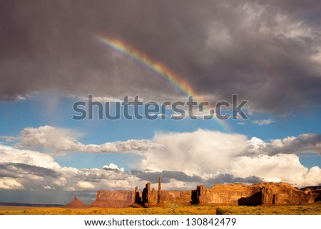 Rainbow and sunlight brighten Monument Valley after the storm - stock photo