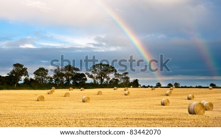 Rainbow appears in the cloudy sky after the rain - stock photo