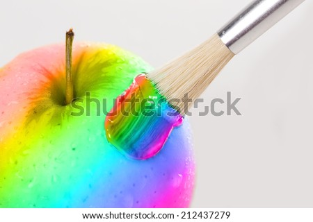 Rainbow apple close-up with water drops being painted on white background - stock photo