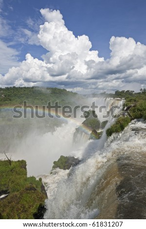Rainbow arch over the cataracts of the Iguazu Falls in the Iguazu National Park - stock photo