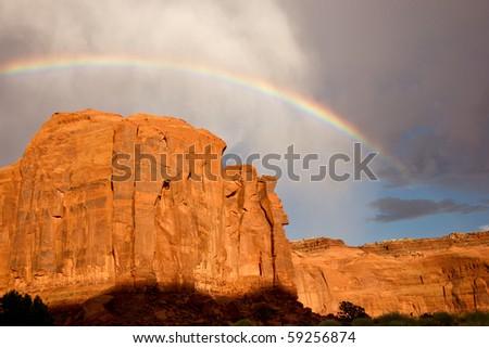 Rainbow arches above massive sandstone cliffs - stock photo