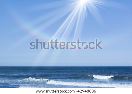 Rainbow around the shining sun over the sea - stock photo