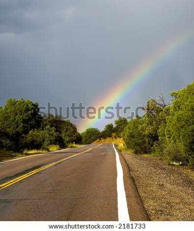 Rainbow at the end of the road - stock photo