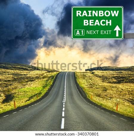 RAINBOW BEACH road sign against clear blue sky - stock photo