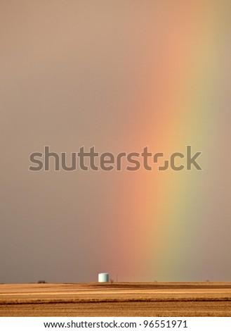 Rainbow behind silo in scenic Saskatchewan - stock photo