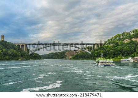 Rainbow Bridge at Niagara Falls - international steel arch bridge across the Niagara River - world-famous tourist site. It connects cities of Niagara Falls, New York (USA) and Niagara Falls (Canada). - stock photo
