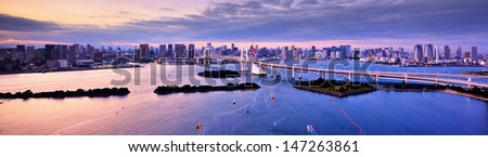Rainbow Bridge spanning Tokyo Bay with Tokyo Tower visible in the background. - stock photo