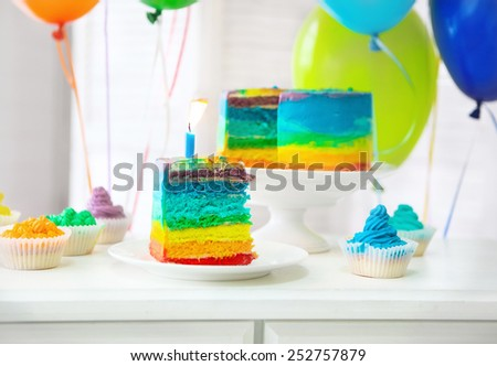 Rainbow cake and cupcakes decorated with birthday candle. Balloons on the background - stock photo