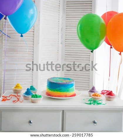 Rainbow cake and cupcakes on the Birthday party. Balloons on the background - stock photo