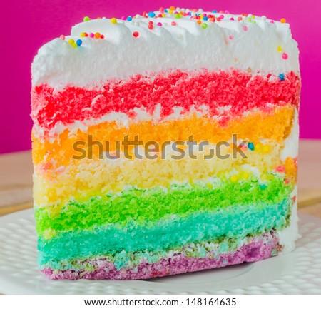 Rainbow cake in white dish - stock photo