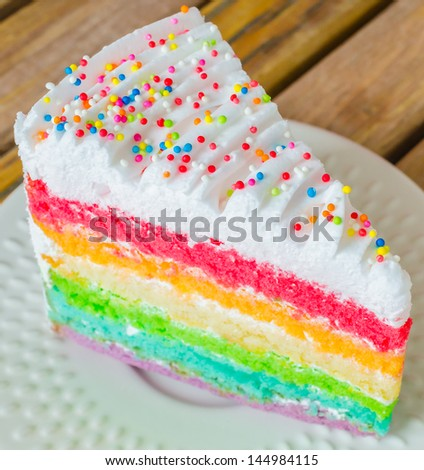 Rainbow cake in white dish on the wood table - stock photo