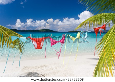 rainbow colored bikinis hanging on tropical beach - stock photo