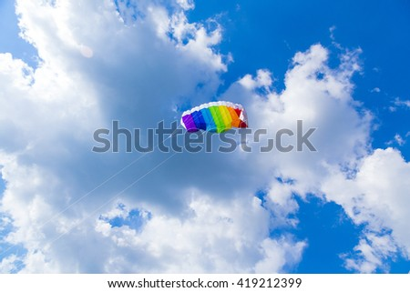 rainbow colored child's kite on blue sky with clouds, natural background