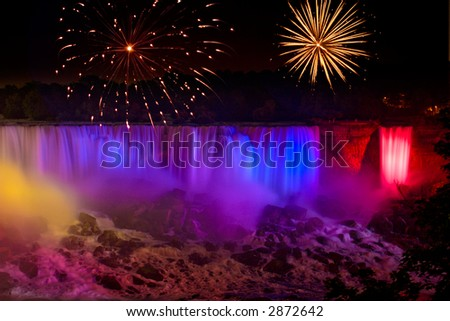 Rainbow colored Niagara Falls with fireworks display - stock photo