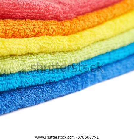 Rainbow colored pile of towels isolated - stock photo