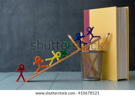 Rainbow colored pipe cleaner people stand and climb ready for learning. With an antique black board and natural window light this is delightful for a variety of educational ideas and concepts - stock photo