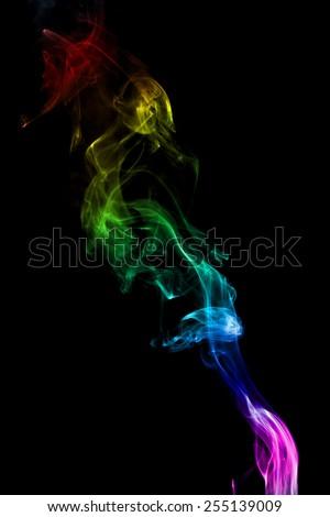Rainbow colored smoke isolated on black background - stock photo