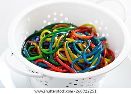 Rainbow colored spaghetti in a white colander - stock photo