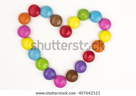 rainbow colored sugar coated candies in heart shape - stock photo