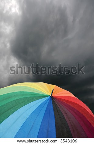 rainbow colored umbrella's in heavy rain to use as background - stock photo