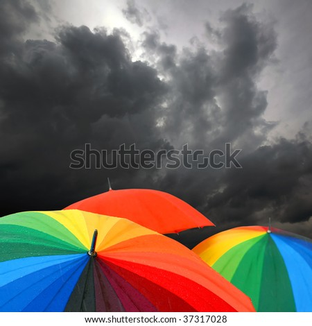 Rainbow colored umbrellas and dark cloudy sky in autumn time on square background - stock photo