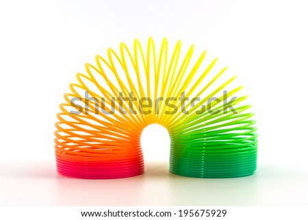 Rainbow colored wire spiral toy on white background. - stock photo