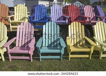 Rainbow colored wooden chairs, known as Maine Chairs, standing in a row outside on the Eastern Shore, Maryland - stock photo