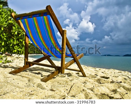 rainbow colour day bed in the sand - stock photo