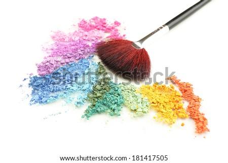 Rainbow crushed eyeshadow and professional make-up brush isolated on white - stock photo