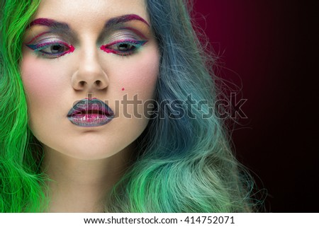 Rainbow dash. Closeup portrait of a gorgeous woman with green and turquoise hair looking away wearing multicolored eye shadow and lipstick