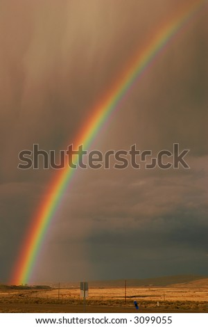 Rainbow emerging from the town of Elko, Nevada, in a rain storm over farmland and desert - stock photo