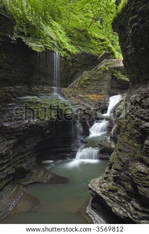 Rainbow Falls at Watkins  Glen state park in New York. Lush green spring colors along the stream add to the beauty of the scene.  One of many waterfalls in my collection.