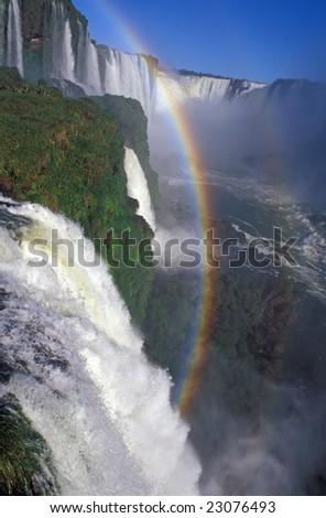 Rainbow formed by the spray of Iguacu Falls, Brazil. - stock photo