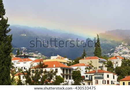 Rainbow formed in the mist and cloud of the mountains over Funchal, Madeira, Portugal