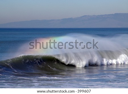 Rainbow forms on wave - stock photo