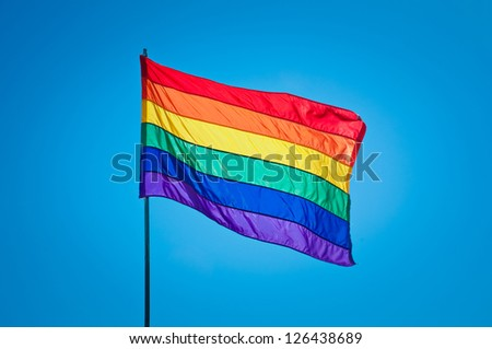Rainbow Gay Pride Flag on blue sky background, Miami Beach, Florida, USA - stock photo