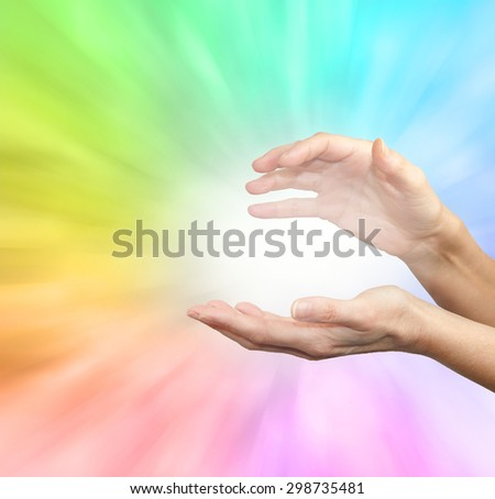 Rainbow healing energy field - Female outstretched healing hands on soft rainbow energy background - stock photo