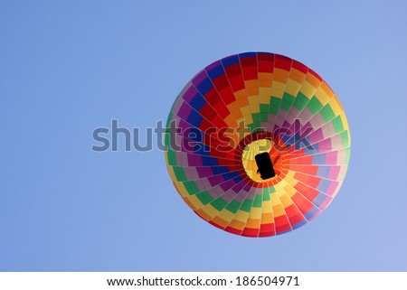rainbow hot air balloon in a blue sky seen from below.  - stock photo