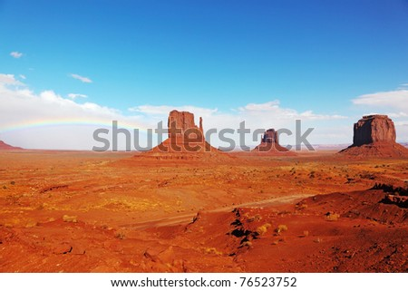 """Rainbow in a red desert. The famous """"Mittens"""" in Monument Valley after the rain - stock photo"""