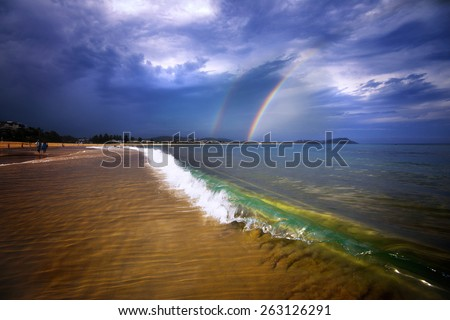 Rainbow in a storm with beautiful waves on the beach - stock photo