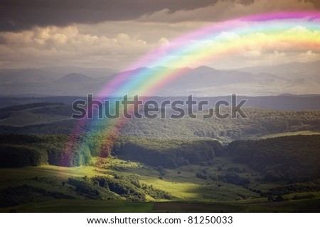 rainbow in a summer landscape - stock photo