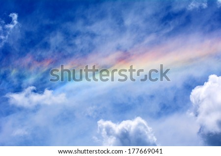 Rainbow in blue cloudy sky. - stock photo