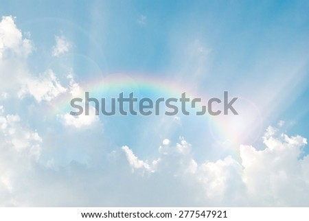 rainbow in the blue sky after the rain with lighting flare - stock photo