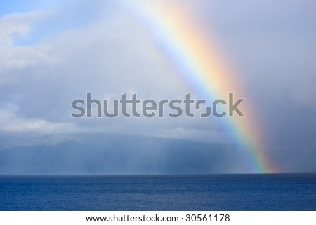 Rainbow in the clouds ending in the ocean Maui - stock photo
