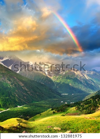 Rainbow in the mountain valley after rain. Beautiful landscape - stock photo