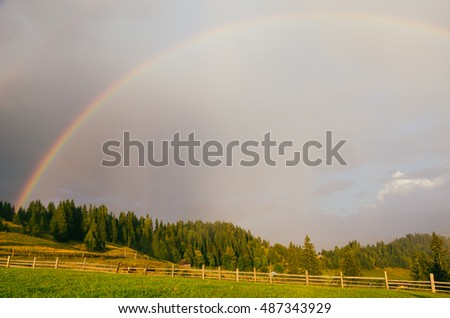 Rainbow in the mountain valley after rain. Beautiful landscape